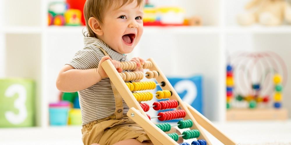 Junge spielt mit einem farbenfrohen Holzabakus