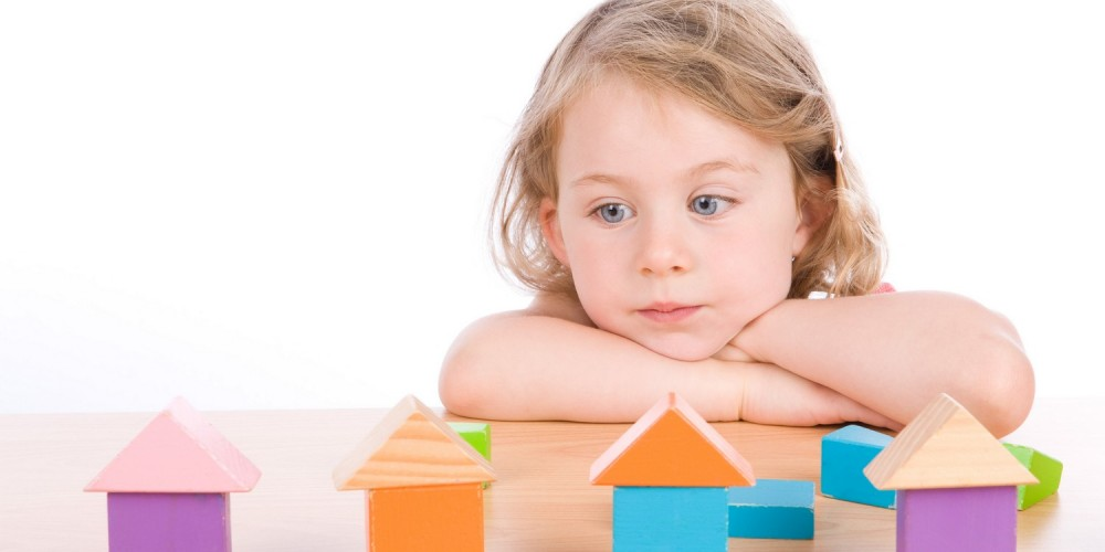 Mädchen hat aus Holzklötzen Häuser gebaut