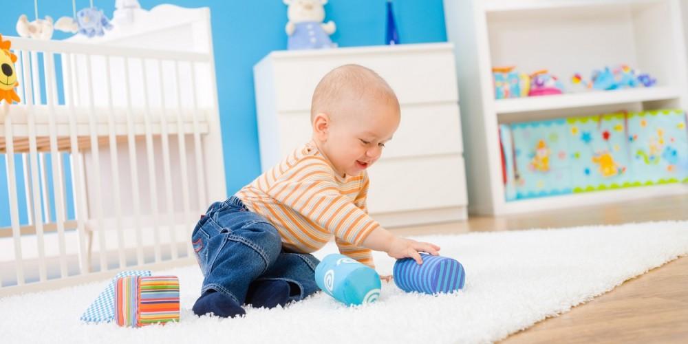 Baby beim Spielen auf einem Teppich