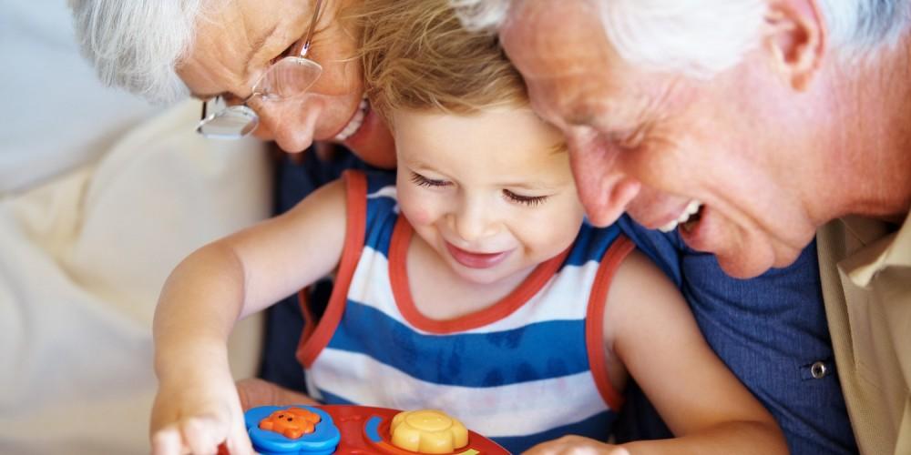 Großeltern gucken ihrem Enkel beim Spielen zu