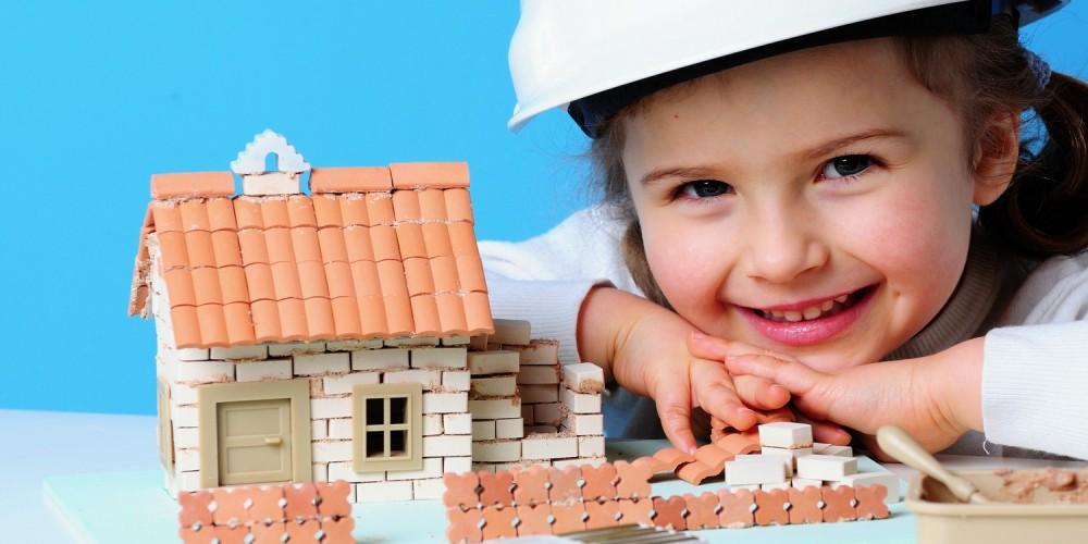 Mädchen mit Bauarbeiterhelm und Spielzeughaus