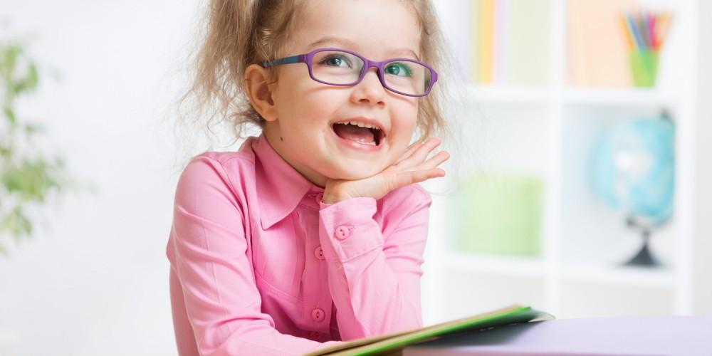 Kleines Mädchen mit Zöpfen und lila Brille sitzt mit Büchern an einem Tisch und träumt vor sich hin