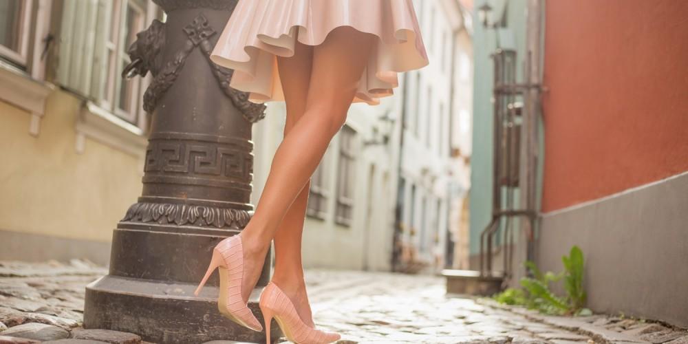 Frau mit schlanken Beinen läuft in kurzem Kleid und rosa Pumps durch eine schmale Gasse in der Altstadt