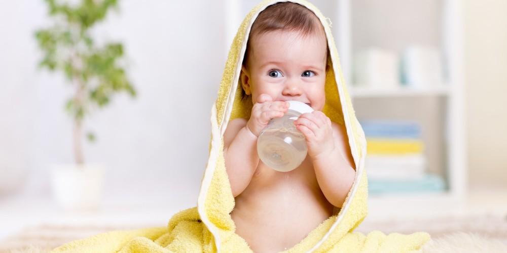 Baby in gelbem Handtuch und mit Fläschchen