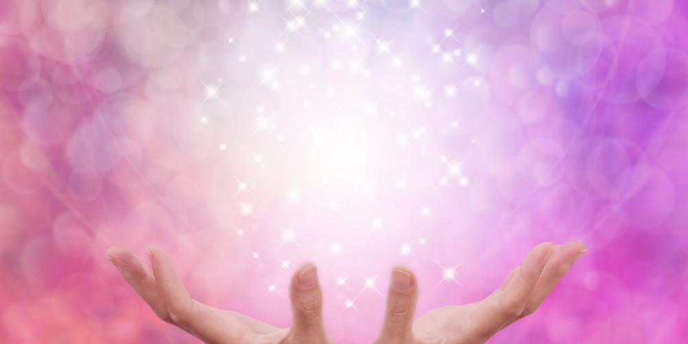Zwei aufgehaltene Hände vor pinkem abstrakten Hintergrund verströmen Licht nach oben