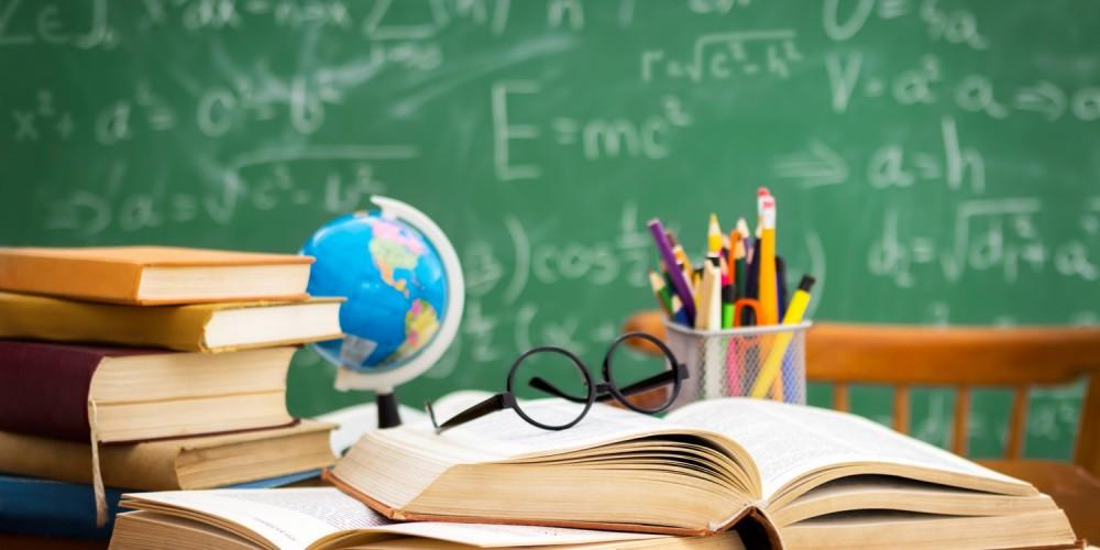 Schreibtisch voll mit aufgeschlagenen Büchern, einer Brille, Stiften und Globus, im Hintergrund eine Tafel