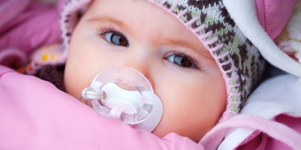 Baby mit Schnuller und Mütze