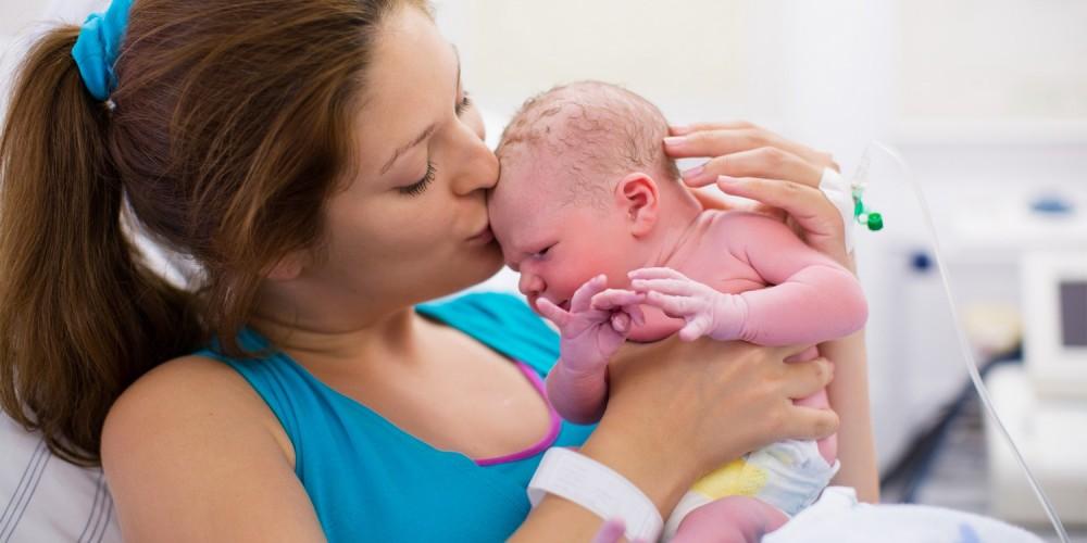 Glückliche Mutter hält ihr Neugeborenes auf dem Arm