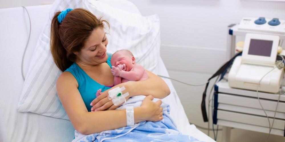 Frischgebackene Mutter sitzt mit ihrem Säugling im Krankenbett