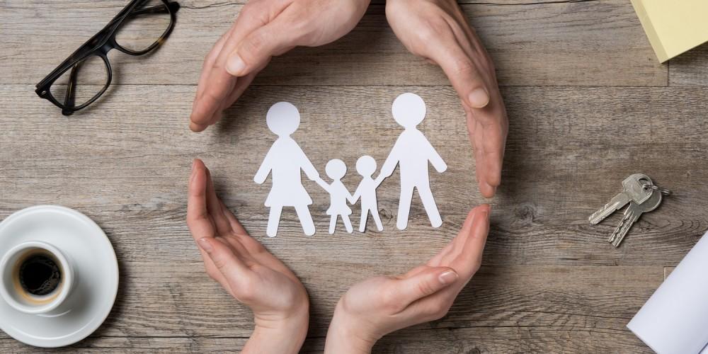 Zwei Händepaare umschließen eine vierköpfige Familie aus Papierfiguren auf einem Holztisch