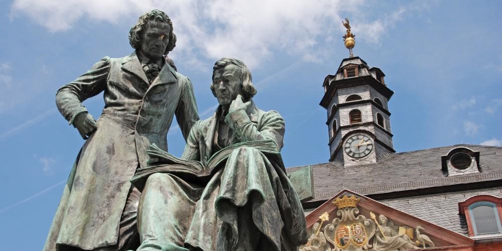 Brüder-Grimm-Nationaldenkmal vor dem Neustädter Rathaus in Hanau unter blauem Himmel
