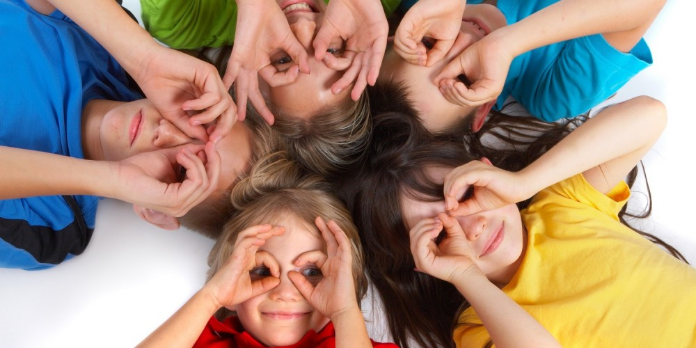Fünf Kinder liegen im Kreis auf dem Boden, halten Hände um Augen und schauen hoch in Kamera