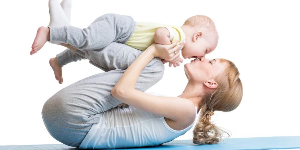 Mutter und Baby bei Fitnessübungen auf einer blauen Yogamatte