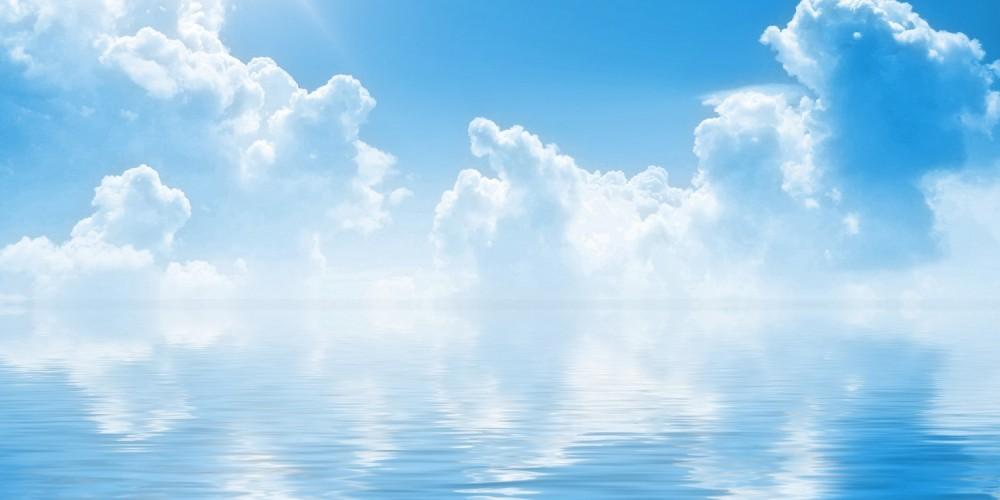 Blauer Himmel, weiße Wolken, Sonnenschein über Wasser