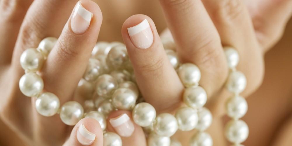 Hände halten eine Perlenkette