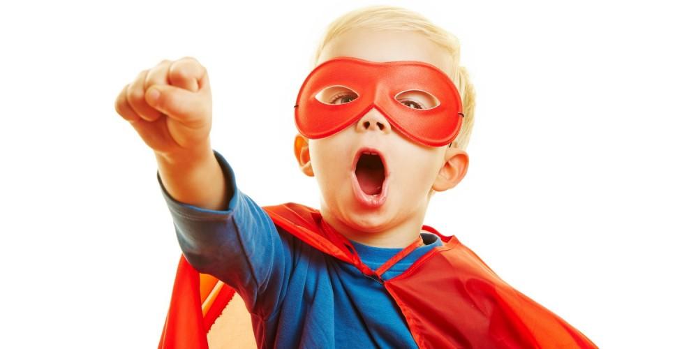 Junge mit Umhang und Maske als Superman verkleidet