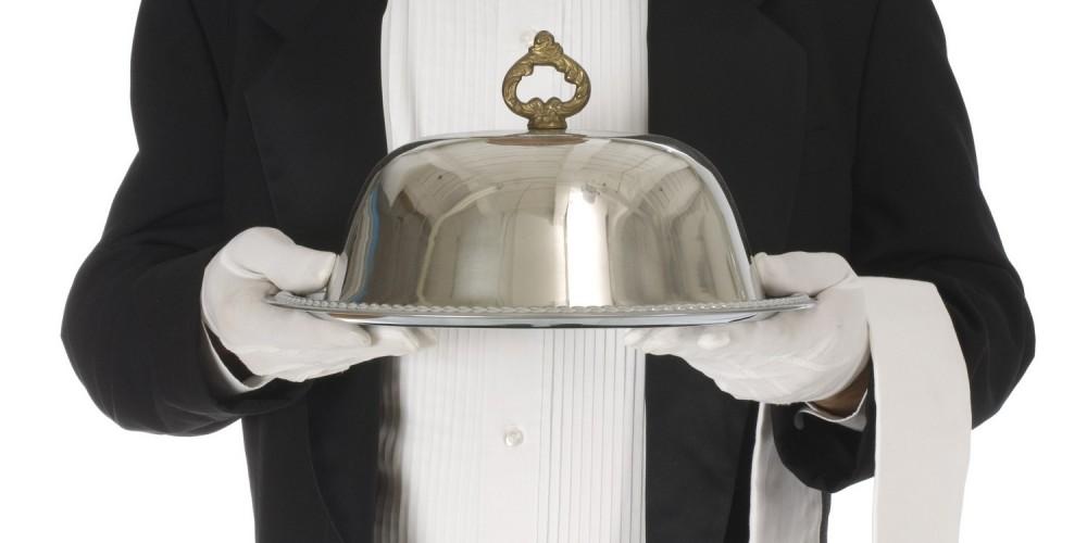 Kellner in schwarzem Smoking und weißen Handschuhen Trägt Essen auf Silbertablett mit Deckel