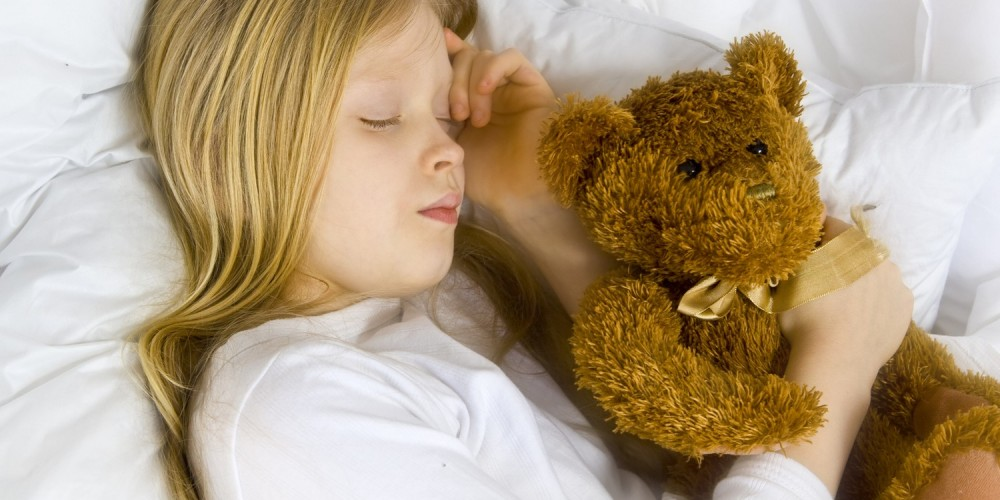 Blondes Mädchen liegt auf der Seite, hält ihren Teddy im Arm und schläft