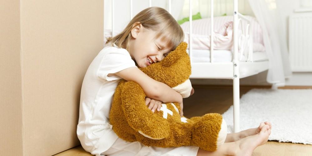 Weinendes Mädchen sitzt neben ihrem Bett