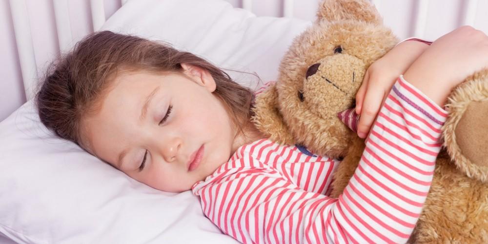 Mädchen schläft mit Teddy im Arm