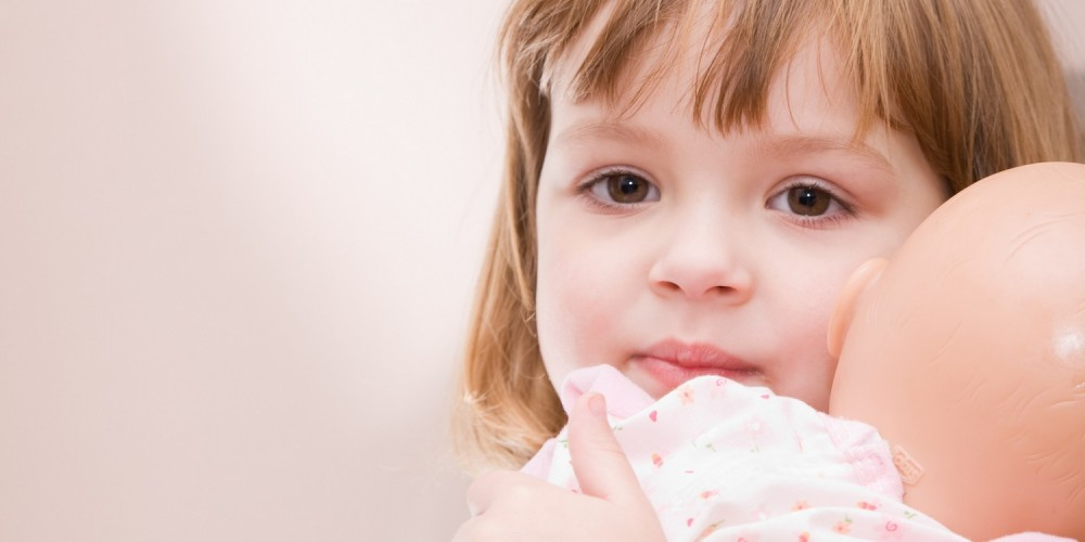 Kleines Mädchen klammert sich an ihren Teddybär